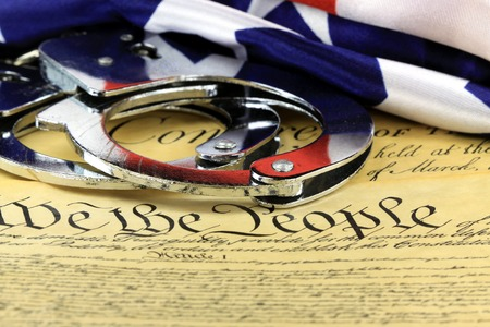 constitutional law: Handcuffs and American flag on US ConstitutionFourth Amendment