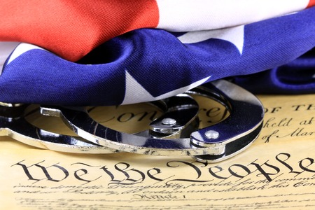 unlawful act: Handcuffs and American flag on US Constitution-Fourth Amendment