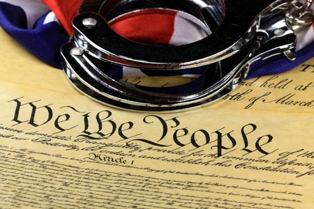 unlawful act: Handcuffs and American flag on US ConstitutionFourth Amendment
