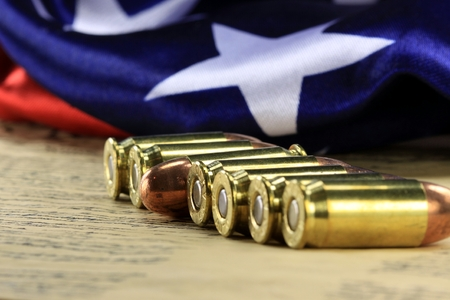 45 caliber: Row of 45 caliber ammunition with US flag in background Stock Photo