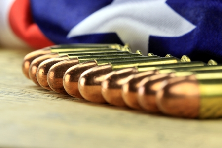 caliber: Row of 45 caliber ammunition with US flag in background Stock Photo
