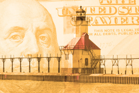 art abstract: Double exposure St. Joseph north pier lighthouse along shoreline of Lake Michigan with hundred dollar bill background