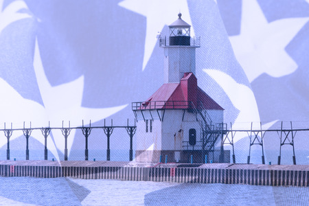 michigan flag: Double exposure St. Joseph north pier lighthouse along shoreline of Lake Michigan with American flag background Stock Photo