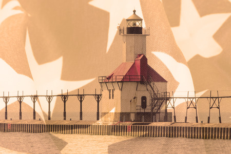 lake michigan lighthouse: Double exposure St. Joseph north pier lighthouse along shoreline of Lake Michigan with American flag background Foto de archivo