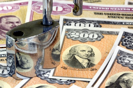investment security: Padlock on top of USA Treasury Savings Bonds - Business Investment security