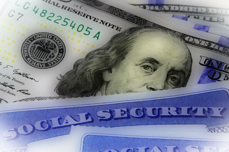 Social security card and US currency one hundred dollar bill - Retirement Concept Social Security Benefits