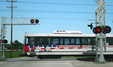 Light rail train passing through an at-grade crossing photo