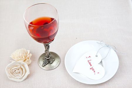Glass with wine and Valentine heart  photo