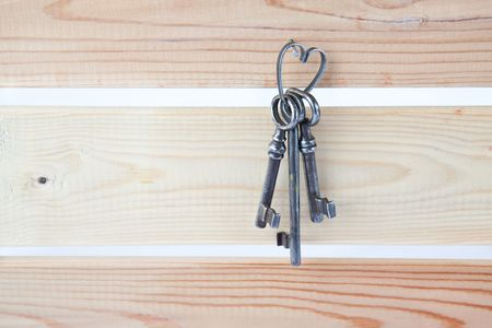 Three old keys on a wooden wall photo