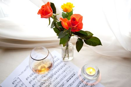 Bouquet of beautiful rose with musical notes and brandy glass photo