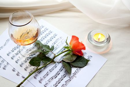 Beautiful red rose with music notes, glass and burning candle photo