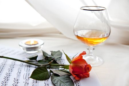 Beautiful red rose on the notes with glass and burning candle  photo