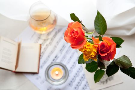Three beautiful roses with book, music notes and burning candle photo