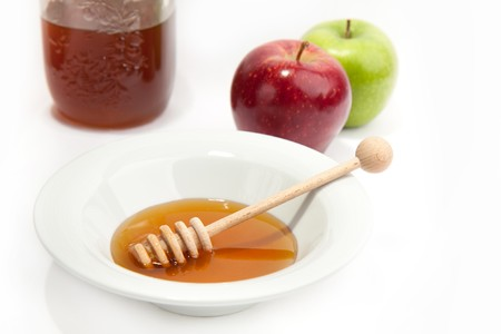 Honey with wood stick pouring and apples  photo