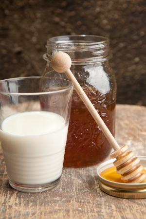 Milch und frischem Honig mit Holz stick Gießen