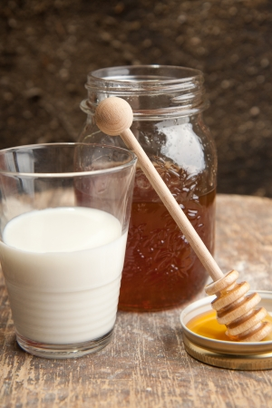 Milk and the fresh honey with wood stick pouring