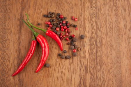 Red chili pepper and peppers mix on the wooden desk photo