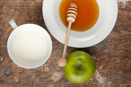 Breakfast with milk, honey and apple on the old wooden table photo
