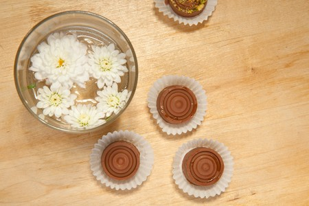 Homemade sweet chocolate and white flowers on the wooden table photo