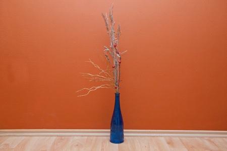 Bouquet in blue bottle on a floor near the orange wall Stock Photo - 8308840