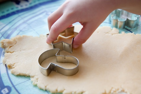 The young boy on a kitchen cut the cookies from the dough photo