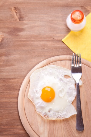 frog egg: Fried egg served on a wooden table with salt and frog Stock Photo