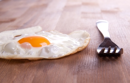 frog egg: Fried egg served on a wooden table with a metal frog