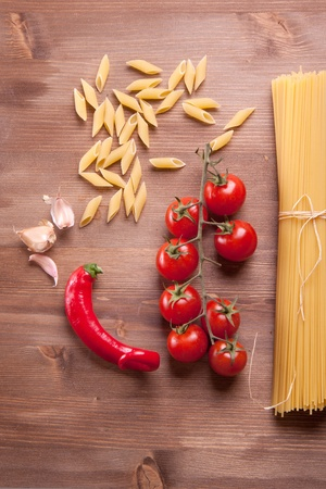 Composition of tow kind of pasta, pepper, onion and tomato photo