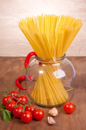 Bunch of spaghetti in the glass pot with cherry tomato, chili peppers and onion photo