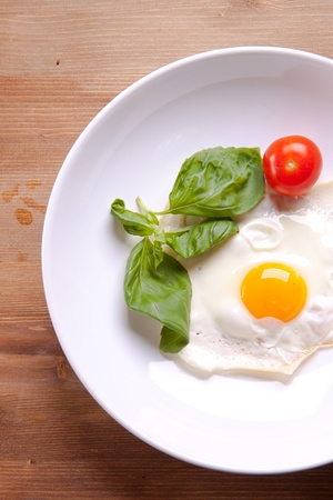 Fried egg served on a white plate with tomato and fresh herbs