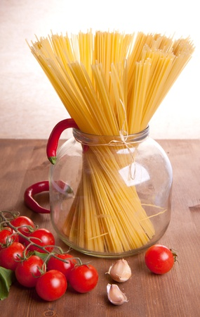 Composition of pasta, garlic, pepper and tomato on a wooden table photo