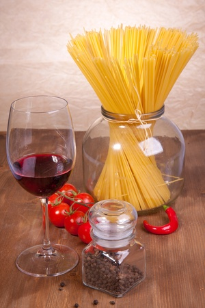 Composition of pasta, pepper, tomato and glass of red wine on the wooden table photo