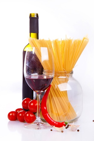 Glass of red wine near italian spaghetti and vegetables for pasta photo