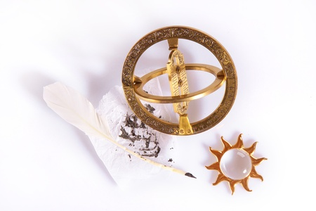 Composition of old measuring instrument for navigation, white feather and golden sun