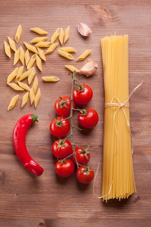 Composition of tow kind of pasta, chili pepper, onion and tomato photo