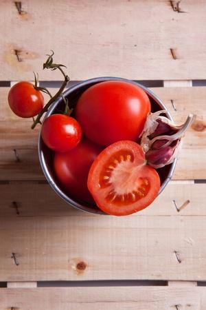 トマトと木製の机の上の金属製のバケツでニンニクのミックス
