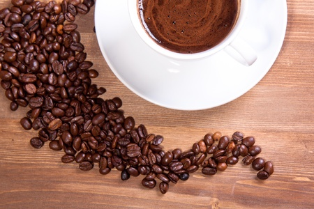 Cup of black coffee and fragrant fried coffee beans on a wooden table photo