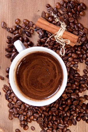 Cup of black coffee and fragrant fried coffee beans and cinnamon on a wooden table