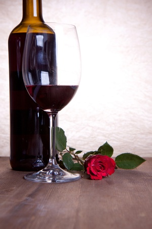 bottle and glass with red wine and beautiful red rose photo