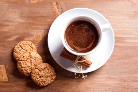 White cup of black coffee with cinnamon and cookies photo