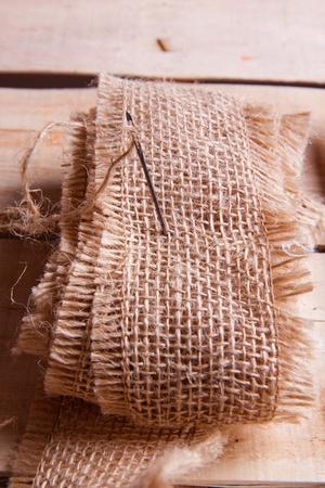needle and jute thread on wooden desk photo