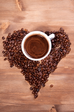 White cup of black coffee with coffee beans as a heart photo