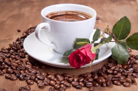 Blanco taza de café negro con granos de café y Rosa Roja Foto de archivo
