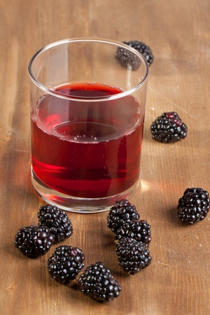 Fresh blackberries and glass of juice on wooden table photo