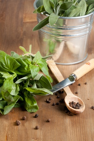 trituration: Fresh herbs with pepper, knife and spoon on wooden table Stock Photo