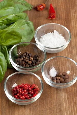 Salt and peppers mix with fresh herb on the wooden desk photo