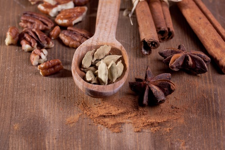 pekan: mix of spice cinnamon, anise, pekan, cardamom in wooden spoon on wooden table Stock Photo
