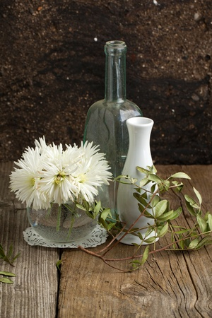 Composition with bouquet of white flowers with vase and bottle on old wooden table photo