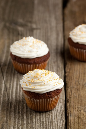 Cupcakes with whipped cream on old wooden table photo