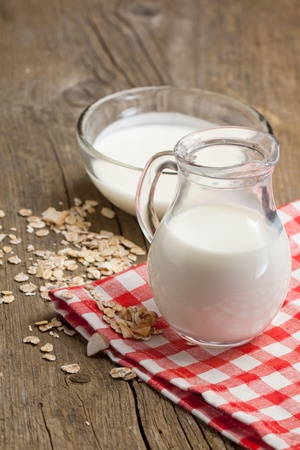 Transparent jug of milk with muesli and bowl of yogurt on old wooden table photo